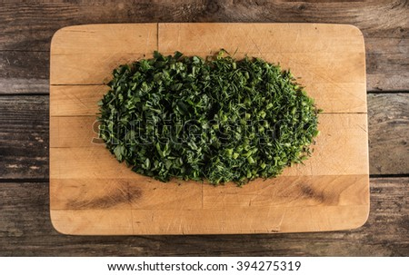 parsley and dill on chopping board - stock photo