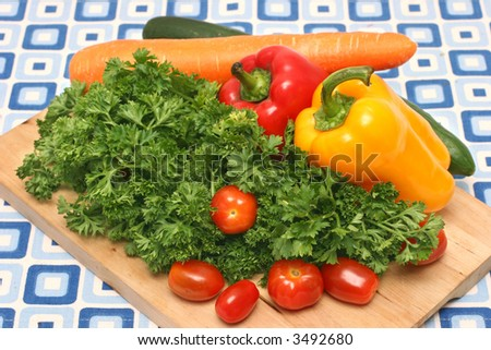 Parsley, cherry tomatoes, capsicums, carrot and cucumber on wooden board
