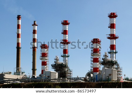 Part of a big oil refinery and powerplant  against blue sky showing some new equipment - stock photo