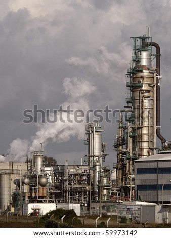 Part of a big oil refinery seeing steam - stock photo