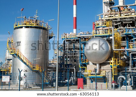 Part of a big oil refinery with many silver pipes and machinery - stock photo