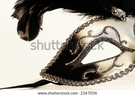 Part of a black and silver mask on a white background