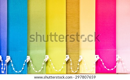 Part of a blind with multiple colours as a background