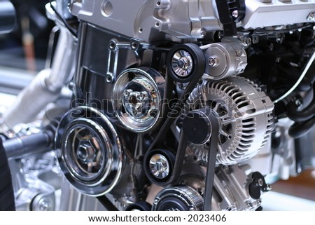 Part of a car engine. Some of the gears are spinning.