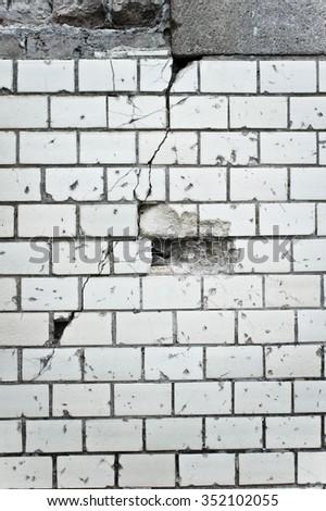 Part of a damaged white brick wall - stock photo