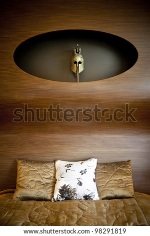 Part of a design bedroom with an ancient greek mask and pillows. - stock photo