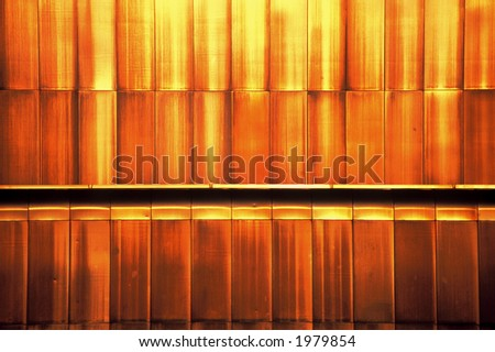 Part of a facade cladding of a commercial building illuminated by evening sunlight.