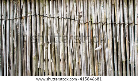 Part of a fence made of dried reeds - stock photo