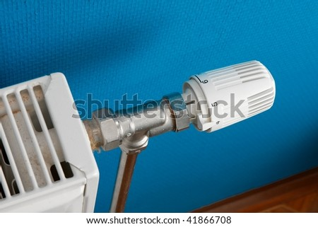 Part of a heating radiator against blue wall - stock photo