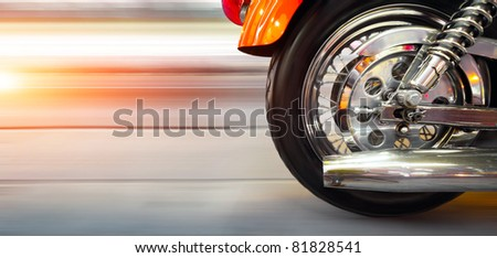 Part of a luxury motorcycle with blurry asphalt road - stock photo