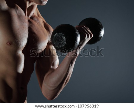 Part of a man's body with metal dumbbell on a grey background