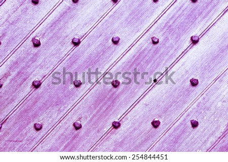 Part of a medieval door with metal studs with purple filter applied - stock photo