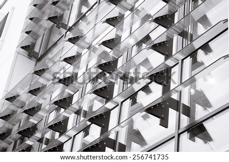 Part of a modern building with glass panels in black and white - stock photo