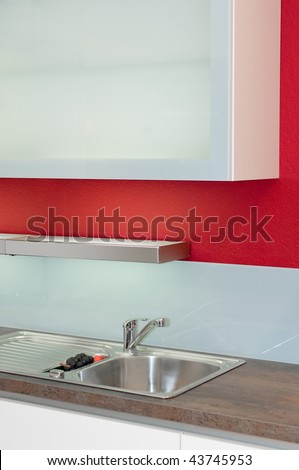 Part of a modern kitchen with white furniture an red wall - stock photo