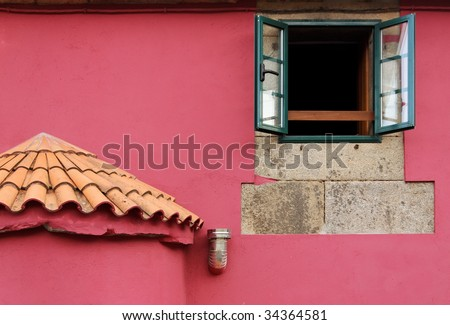 Part of a pink wall with an open window. - stock photo