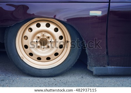 Part of a purple car with pneumatic suspension on the pavement. Car wheel, closeup
