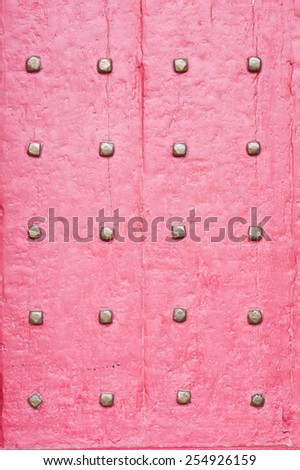 Part of a red medieval door with metal studs - stock photo