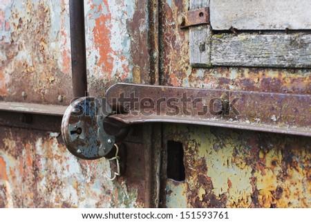 Part of a rusty metal door closed old lock - stock photo