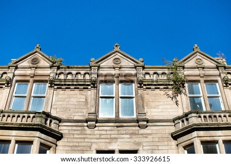 Part of a stone building against a blue sky in Elgin, Scotland