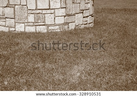 part of a stone structure or brick wall from a natural stone on a lawn for abstractions and a blank space for the text