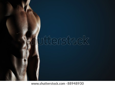 Part of a wet man's body on a dark blue background with copyspace - stock photo