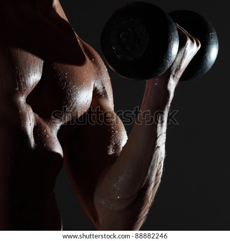 Part of a wet man's body with metal dumbbell on a gray background - stock photo