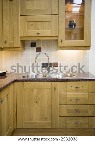 Part of a wooden kitchen with a stainless steel sink