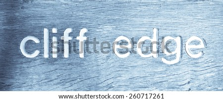Part of a wooden sign indicating a nearby cliff edge in Suffolk, UK in cold tones - stock photo