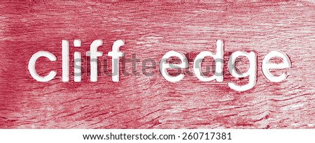 Part of a wooden sign indicating a nearby cliff edge in Suffolk, UK, in red tones - stock photo