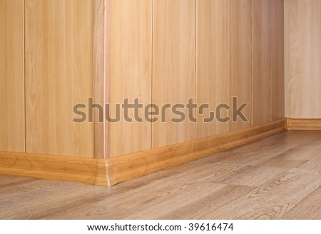Part of a wooden wall and floor with a parquet