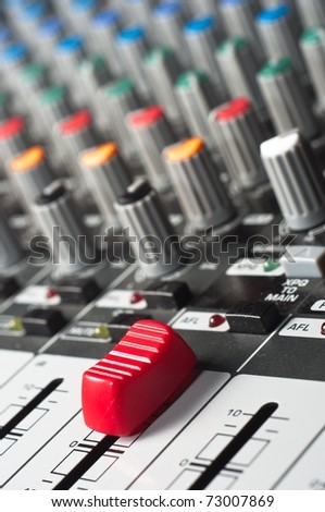 Part of an audio sound mixer with buttons and a slider - stock photo