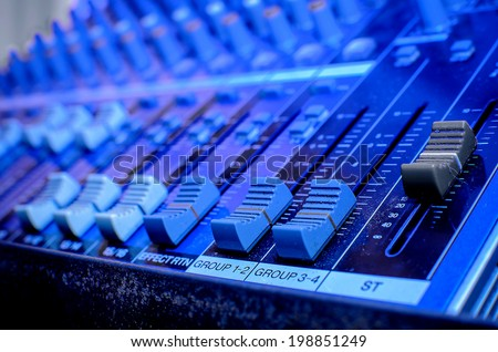 Part of an audio sound mixer with buttons and sliders - stock photo