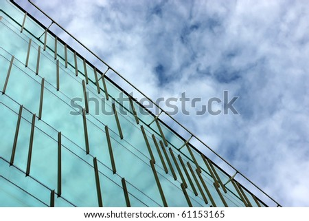 Part of an office building facade reflecting the sky and clouds