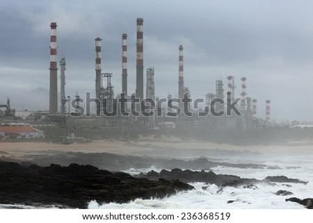 Part of an oil big refinery near the sea in the middle of smog - stock photo