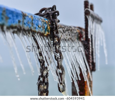 Part of an old pier covered with ice/icicles and with fragment of anchor chain. Selective focus.