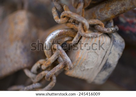 Part of an old rusted chain with a padlock - stock photo