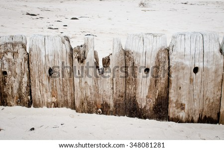 Part of an old wooden fence on a beach with severe wood damage due to moisture - stock photo