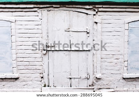 Part of brick wall with old locked door and windows - stock photo