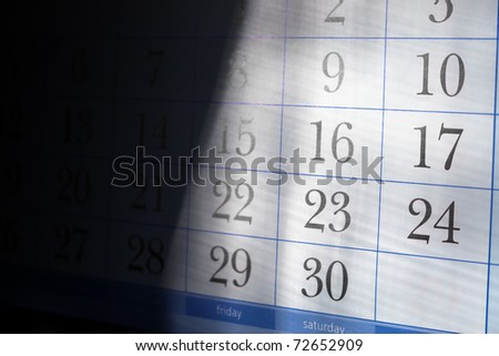 Part of calendar with month end dates with shallow depth of field and half in deep shadow - stock photo