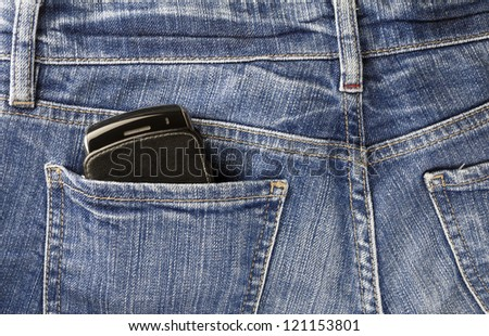Part of cellphone in the back pocket of blue jeans - stock photo