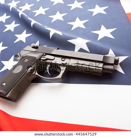 Part of close up studio shot of national flag with hand gun over it series - United States - stock photo