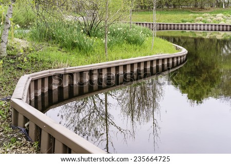 Part of curved retaining wall around pond in springtime - stock photo