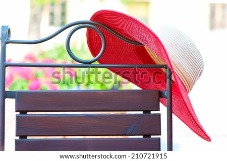 Part of elegant metal curved chair and red summer hat on patio. Outdoors. - stock photo