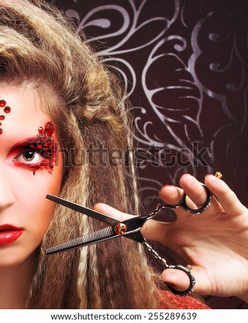 Part of face of young woman in creative image and with scissors - stock photo