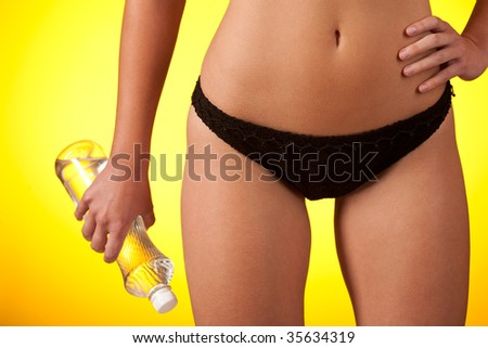 Part of female body wearing black bikini  and holding bottle of water on yellow background