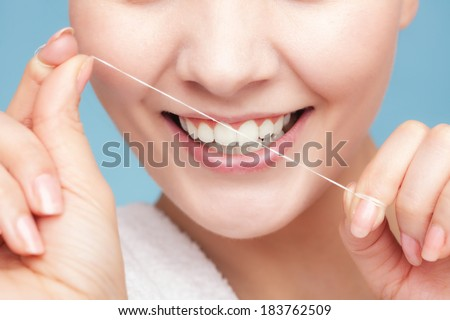 Part of female face. Young woman smiling girl cleaning her white teeth with dental floss on blue. Daily health care. Studio shot. - stock photo