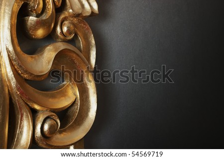 Part of golden stucco decoration in curve shape against dark wall with copy space