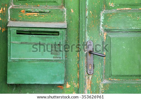 Part of green aged shabby door and postbox - stock photo