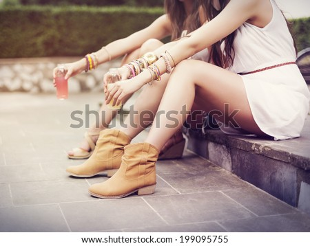 Part of hippie women sitting on curb - stock photo