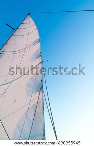 Part of hoisted mainsail of sailing boat with leech, rigging and reefing lines against blue sky